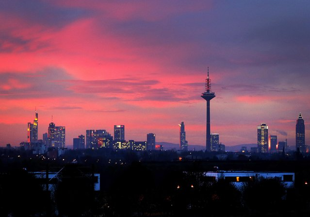 Colorful clouds hang over the skyline as the sun rises in Frankfurt, Germany, Tuesday, Nov. 22, 2016. (Photo by Michael Probst/AP Photo)