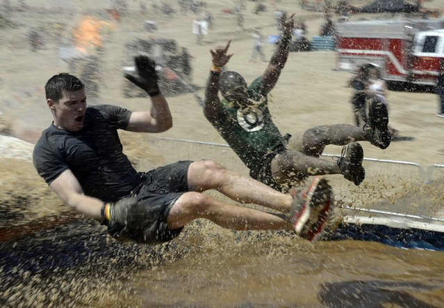 "People hit muddy waters at full speed during the ""Tough Mudder"" obstacle course event in San Bernardino, California in this March 29, 2014 file photo. (Photo by Gene Blevins/Reuters)"