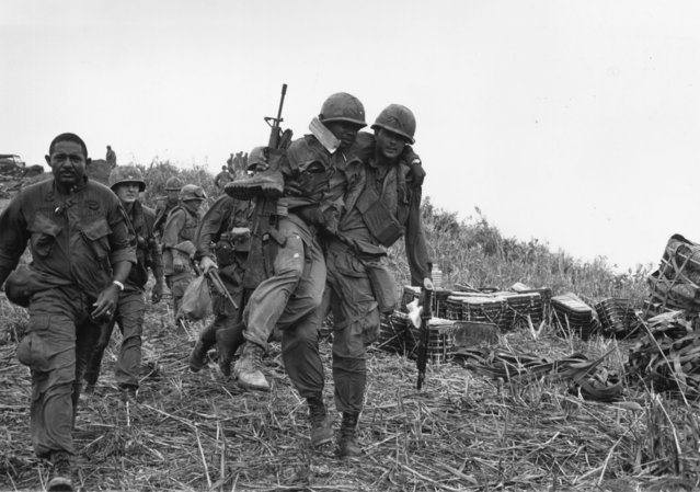 US soldiers, one wounded and being carried by a colleague, walking down Hill Timothy, during the conflict in Vietnam, 11th April 1968. (Photo by Terry Fincher/Daily Express/Hulton Archive/Getty Images)