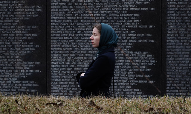 A woman visits the memorial walls at Butovo shooting range outside Moscow, Russia, 30 October 2020. The Memory Garden memorial was unveiled and blessed on 27 September 2017, in memory of 20,762 people executed here during Stalin political terror in 1937-1938. The victims were executed on allegations ranging from their Chiristian faith, non-proletarian social origin, or political views. Apple garden was planted in the 70s by Soviet KGB servicemen on the site of the mass executions. (Photo by Maxim Shipenkov/EPA/EFE)