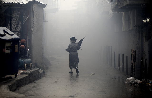 An Ultra-Orthodox Jewish man walks down a street through the smoke from burning leavened items during the Srefat Chametz ritual on March 30 2018 in Jerusalem on the eve of the Jewish Pesach (Passover) holiday, which begins at sunset today. Due to the haste with which the Jews left Egypt, the bread they had prepared for the journey did not have time to rise. To commemorate their ancestors' plight, the religious avoid eating leavened food products throughout Passover. (Photo by Menahem Kahana/AFP Photo)