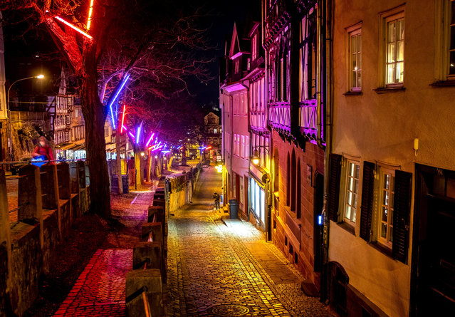 Christmas lights hang in the trees as the streets are almost empty in the old town of Marburg, Germany, Monday, November 30, 2020. (Photo by Michael Probst/AP Photo)