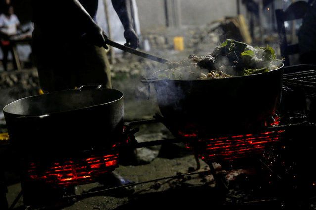 A man cooks on the street after Hurricane Matthew hit Jeremie, Haiti, October 14, 2016. (Photo by Carlos Garcia Rawlins/Reuters)