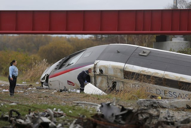 Rescue workers search the wreckage of a test TGV train that derailed and crashed in a canal outside Eckwersheim near Strasbourg, eastern France, November 14, 2015. (Photo by Vincent Kessler/Reuters)