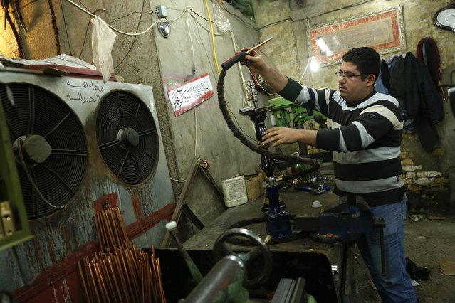 A man works at a shisha manufacturing factory in Baghdad December 17, 2014. (Photo by Thaier Al-Sudani/Reuters)