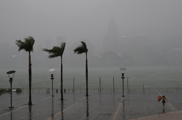 A woman braves the wind on the waterfront of Victoria Habour as Typhoon Haima approaches Hong Kong, Friday, October 21, 2016. (Photo by Vincent Yu/AP Photo)