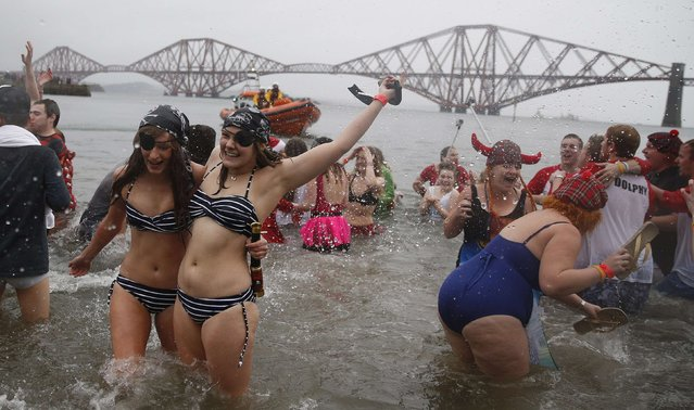 Swimmers in fancy dress splash as they participate in the New Year's Day Loony Dook swim at South Queensferry, Scotland, January 1, 2015. (Photo by Russell Cheyne/Reuters)