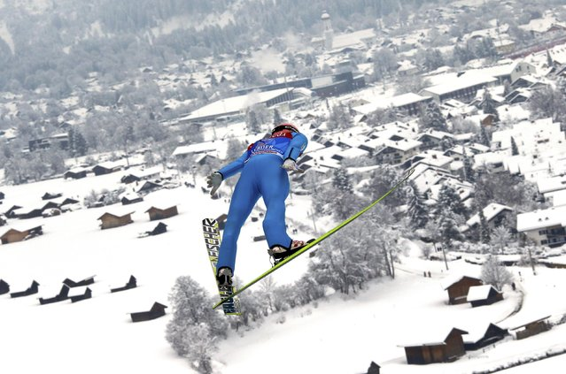 Stefan Kraft from Austria soars through the air during the practice for the second jumping of the 63rd four-hills ski jumping tournament in Garmisch-Partenkirchen, southern Germany, December 31, 2014. The prestigious four-hills tournament will end in Bischofshofen on January 6. (Photo by Michael Dalder/Reuters)