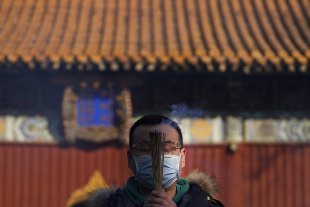A man wearing a face mask to help curb the spread of the coronavirus holds incense offers prayers on the first day of the New Year at Yonghegong Lama Temple in Beijing, Friday, January 1, 2021. President Xi Jinping said in a New Year address that China has made major progress in developing its economy and eradicating rural poverty over the past year despite the coronavirus pandemic. (Photo by Andy Wong/AP Photo)