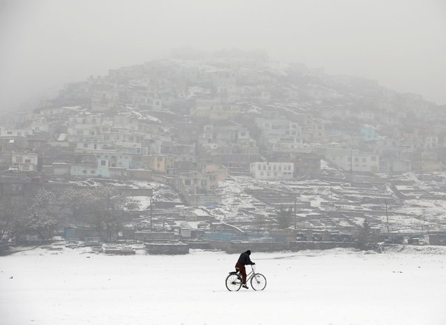 An Afghan man rides a bicycle during snowfall in Kabul, Afghanistan on November 23, 2020. (Photo by Mohammad Ismail/Reuters)
