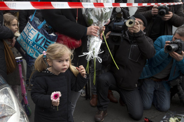 A little girl holds a flower as she accompanies her mother who put flowers outside a kosher market in after an attack in Paris, France, Saturday, January 10, 2015. What started as a hunt for two terror suspects took on an even graver focus Friday as French police grappled with a potential terrorist cell. The suspects knew each other, had been linked to previous terrorist activities, and one had fought or trained with Al Qaida in Yemen. (Photo by Peter Dejong/AP Photo)
