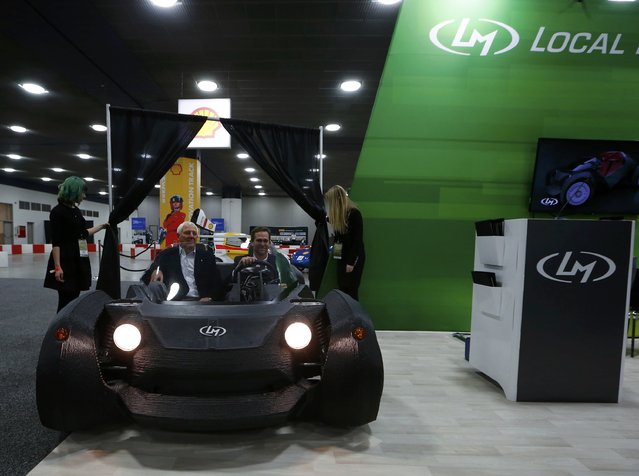 CEO and founder of Local Motors John B. Rogers (driving car) and Milt Peterson, of Peterson Companies, showcase the world's first 3-D printed car, the Strati, during the first press preview day of the North American International Auto Show (NAIAS) in Detroit, Michigan, January 12, 2015. (Photo by Mark Blinch/Reuters)