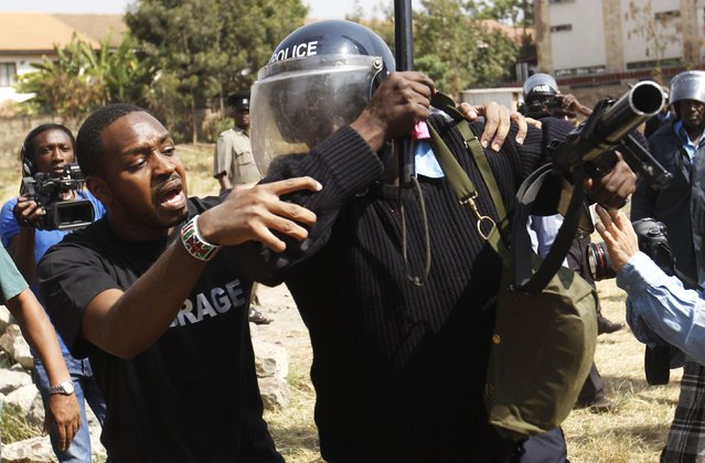 Kenyan activist Boniface Mwangi attempts to help a riot policeman injured in a scuffle during a protest by students of Langata primary school against a perimeter wall erected by a private developer around their school playground in Kenya's capital Nairobi, January 19, 2015. (Photo by Thomas Mukoya/Reuters)