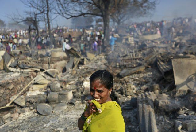 A woman cries as she stands on debris from her gutted hut after a fire occurred in a slum area in Mumbai, India, December 7, 2015. (Photo by Danish Siddiqui/Reuters)