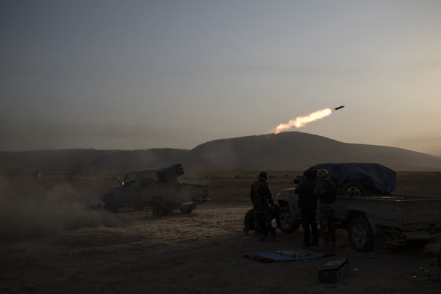 Kurdish Peshmerga soldiers fire artillery at Islamic State positions in Bashiqa, east of Mosul, Iraq, Monday, November 7, 2016. Iraqi Kurdish fighters are exchanging heavy fighters with militants as they advance from two directions on a town held by the Islamic State group east of the city of Mosul. (Photo by Felipe Dana/AP Photo)