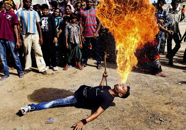 A man performs a fire stunt during Jal Yatra, or the water procession, in Ahmadabad, India, on June 23, 2013. The holy water from the Sabarmati river is carried and used for rituals of the idols of Hindu God Jagannath, his brother Balabhadra and sister Subhadra, which are then carried in a procession in specially made chariots during the Rath Yatra or chariot festival scheduled to be celebrated on July 10. (Photo by Ajit Solanki/Associated Press)
