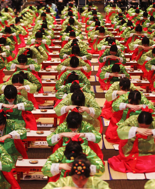"""Students wearing traditional Korean dress, called """"hanbok"""", bow deeply during a traditional coming-of-age ceremony in the central city of Daejeon South Korea, 09 December 2015. (Photo by EPA/Stringer)"""