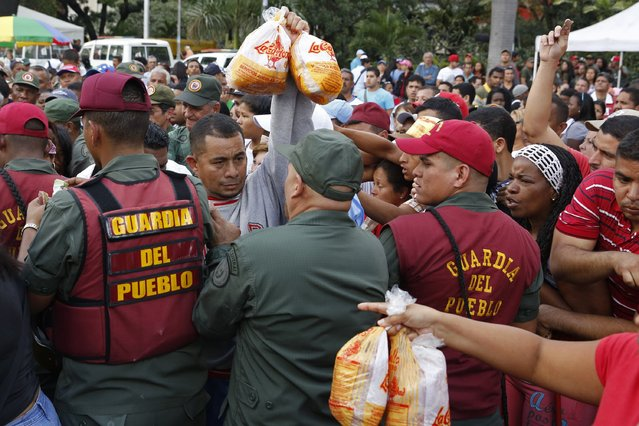 Venezuelan soldiers try to control the crowd as people attempt to buy chickens at a Mega-Mercal, a subsidized state-run street market, in Caracas January 24, 2015. (Photo by Carlos Garcia Rawlins/Reuters)