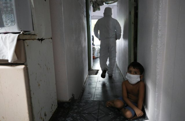 A kid looks on as a municipal healthcare worker walks after examining the body of Shirlene Morais Costa, who died at home at the age of 53 after reporting symptoms consistent with COVID-19 in Manaus, Brazil, January 11, 2021. (Photo by Bruno Kelly/Reuters)