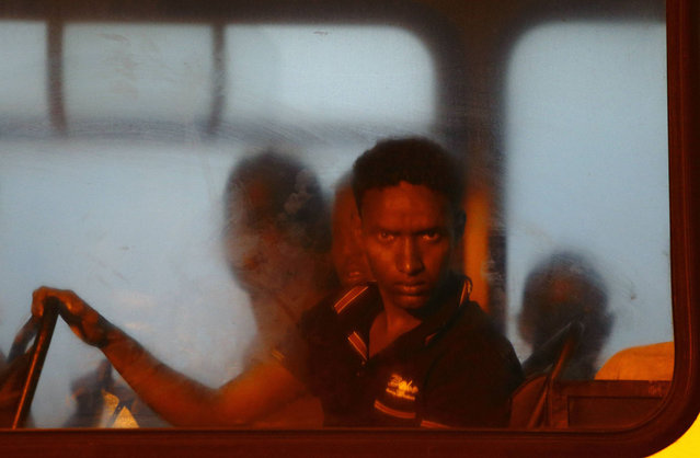 A would-be immigrant looks out of a window on a police bus after arriving at the Armed Forces of Malta (AFM) Maritime Squadron base at Haywharf in Valletta's Marsamxett Harbour early July 10, 2013. Sixty-eight African immigrants were rescued by the AFM, 70 nautical miles south of Malta from a vessel in distress while trying to reach European soil from Africa, according to army sources. (Photo by Darrin Zammit Lupi/Reuters)