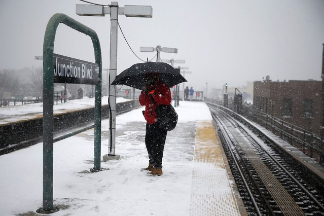 A man stands with an umbrella at the Junction Boulevard stop of the 7 subway train line in the Queens borough of New York January 26, 2015. As a powerful blizzard bears down on the northeastern United States, airlines, commuter rail, bus lines and subways have responded with travel delays and cancellations. (Photo by Shannon Stapleton/Reuters)