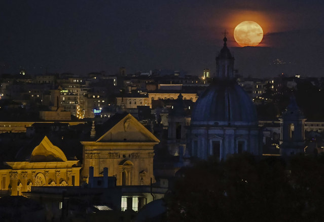 A full moon rises over the Rome's skyline, Monday, November 14, 2016. Monday's supermoon, a phenomenon that happens when the moon is visible in full as it makes a close pass at the earth, is the closest to earth since 1948. (Photo by Alessandro Di Meo/ANSA via AP Photo)