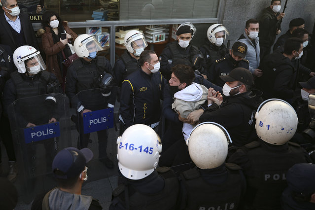 Riot police officers form a corridor as plainclothes police direct detained supporters of Bogazici University students following a protest in Istanbul, Thursday, February 4, 2021. For weeks, students and faculty members of Bogazici University have been protesting Turkey's President Recep Tayyip Erdogan's Jan. 1 appointment as a rector of Melih Bulu, an academic who once ran for parliament as a candidate for Erdogan's party. Some of the protests have erupted into clashes between police and demonstrators and hundreds of people have been detained, some taken away following raids of their homes. (Photo by Emrah Gurel/AP Photo)