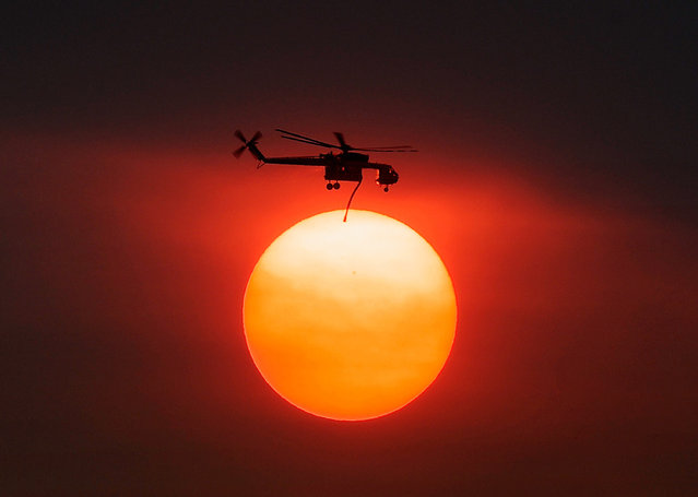 Smoke from the Mountain Fire obscures the sun as a fire fighting helicopter heads to fight the Mountain Fire after picking up water from Lake Hemet July 18, 2013 near Idyllwild, California. The massive wildfire in Riverside County has grown to 23,000 acres and is advancing towards the mountain town of Idyllwild on one front and city of Palm Springs on the other front destroying several homes and forcing the evacuation of 6,000 people.  (Photo by Kevork Djansezian/Getty Images)