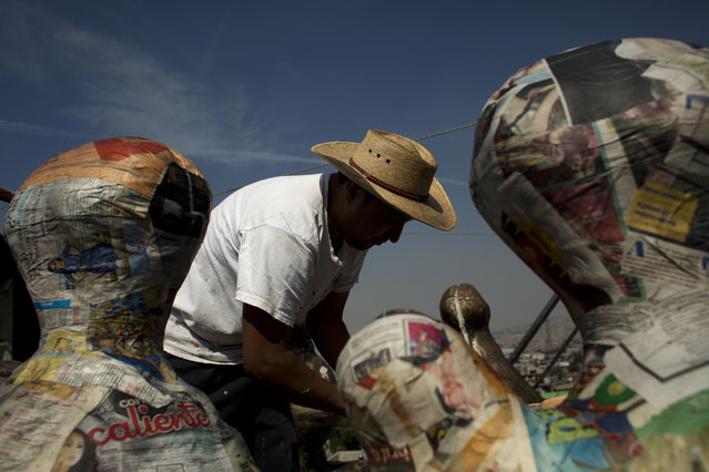 In this January 20, 2015 photo, Guillermo Luna Martinez smoothes strips of newspaper moistened with a glue made from wheat flour onto piñata molds for creating structured piñatas, which involve separate pieces that need to be assembled, on the rooftop of his in-laws' family workshop in the Iztapalapa neighborhood of Mexico City. (Photo by Rebecca Blackwell/AP Photo)