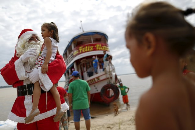 Claudionor Jose de Deus, wearing a Santa Claus costume, arrives at Santa Rosa community to distribute presents to children, on the shores of the Amazon River in rural Manaus, Brazil, December 19, 2015. (Photo by Bruno Kelly/Reuters)