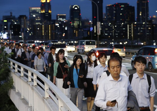 In this June 18, 2018, photo, people walk on a bridge while train and subway service were suspended to check for damage after an earthquake in Osaka, western Japan. The magnitude 6.1 earthquake that struck the area early Monday damaged buildings and left many homes without water or gas. The quake also grounded flights in and out of Osaka and paralyzed traffic and commuter trains most of the day. (Photo by Meika Fujio/Kyodo News via AP Photo)
