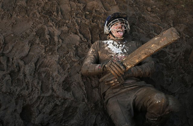 A competitor dressed as a cricketer lies in the mud during the Tough Guy event in Perton, central England, February 1, 2015. (Photo by Phil Noble/Reuters)