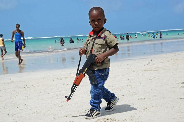 A Somali boy walks with a toy gun along the Lido Beach near Mogadishu, on August 9, 2013. (Photo by Mohamed Abdiwahab/AFP Photo)