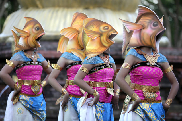 Balinese dancers wearing fish head masks perform as they take part in a cultural parade at a main road in Denpasar, Bali, Indonesia, 28 December 2015. The cultural parade is held to promote tourism in Bali. (Photo by Made Nagi/EPA)