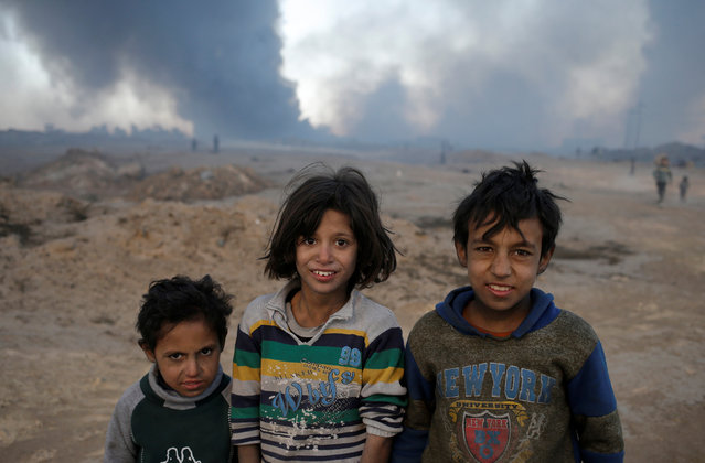 Boys stand in front of oilfields burned by Islamic State fighters in Qayyara, south of Mosul, Iraq November 23, 2016. (Photo by Goran Tomasevic/Reuters)