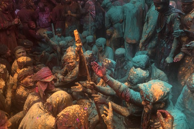 Hindu devotees take part in a traditional gathering during the Lathmar Holi celebrations, the spring festival of colours at a temple in Barsana village of India's Uttar Pradesh state on March 23, 2021. (Photo by Xavier Galiana/AFP Photo)