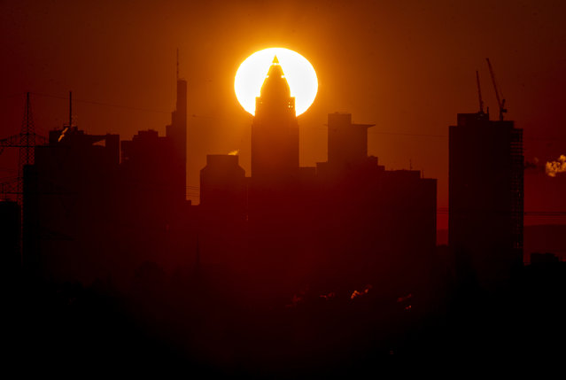 The sun rises behind the buildings of the banking district in Frankfurt, Germany, Saturday, March 6, 2021. (Photo by Michael Probst/AP Photo)