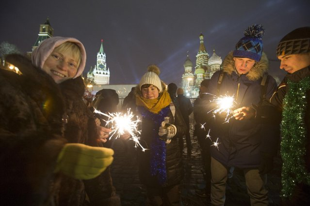 People hold Bengal lights at Red Square during the New Year celebration in Moscow, Russia, Friday, January 1, 2016, with the Spasskaya Tower, left, and St. Basil's Cathedral, right, in the background. Putin is using his New Year's message to commemorate both the country's current fight in Syria and the battles of World War II seven decades ago. The recorded message was being televised just before midnight Thursday in each of Russia's nine time zones. (Photo by Denis Tyrin/AP Photo)