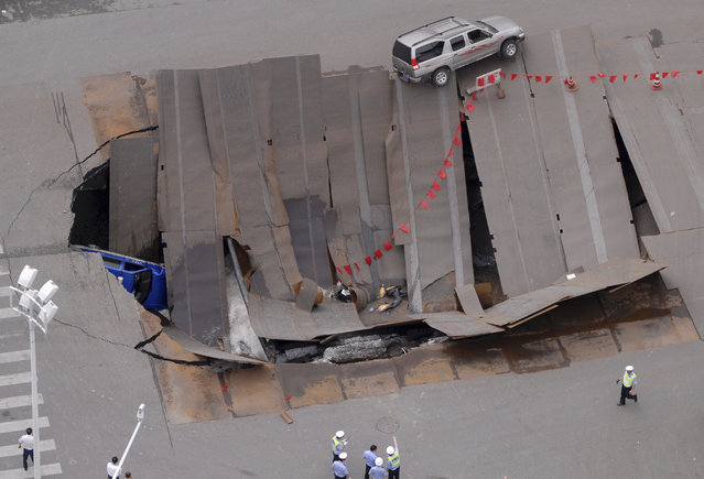 Policemen check a collapsed section of a crossroad in Hefei, Anhui province August 8, 2009. A taxi and a few motorbikes fell into the hole, local media reported. (Photo by Reuters/China Daily)