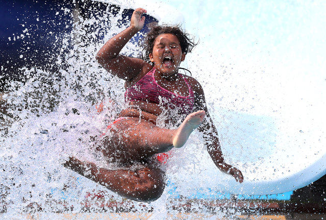 A person jumps into the water as other people refresh at a public pool, in Hanau, Germany on August 12, 2020. (Photo by Kai Pfaffenbach/Reuters)