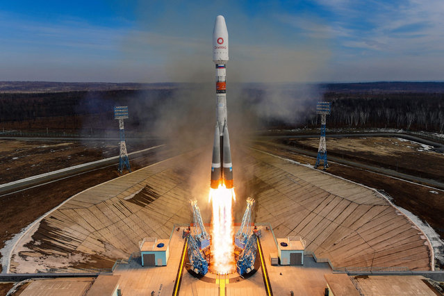 A Soyuz-2.1b rocket booster with a Fregat upper stage and 36 UK telecommunications and internet satellites blasts off from the Vostochny cosmodrome in Russia's Far East on March 25, 2021. (Photo by Handout/Russian Space Agency Roscosmos/AFP Photo)