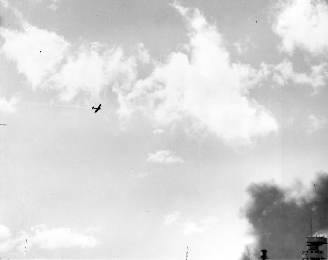 A Japanese Type 00 (Zero) carrier fighter trails smoke after it was hit by anti-aircraft fire during the attack on Pearl Harbor, Hawaii, U.S. December 7, 1941. (Photo by Reuters/U.S. Navy/National Archives)