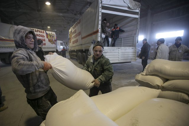 Men carry a sack of flour from a truck, that is part of a Russian humanitarian convoy delivering food, in Donetsk, February 15, 2015. (Photo by Baz Ratner/Reuters)