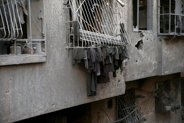 Dust-covered laundry hangs in a damaged site hit by what activists said were airstrikes carried out by the Russian air force in the town of Douma, eastern Ghouta in Damascus, Syria January 10, 2016. (Photo by Bassam Khabieh/Reuters)