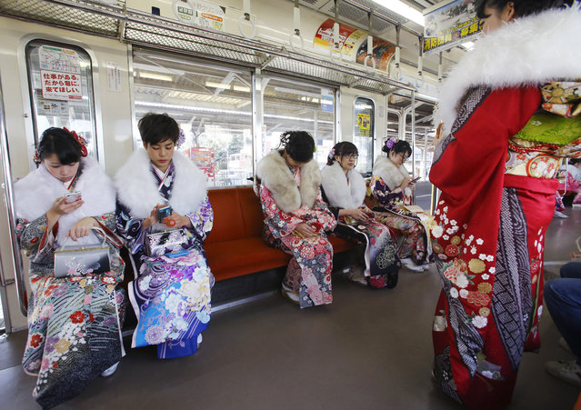 Dressed in Japanese kimonos, a group of Japanese youths who will turn 20 this year, the traditional age of adulthood in Japan, sit in a train after a Coming of Age ceremony at Toshimaen amusement park on the national holiday in Tokyo, Monday, January 11, 2016. (Photo by Shizuo Kambayashi/AP Photo)