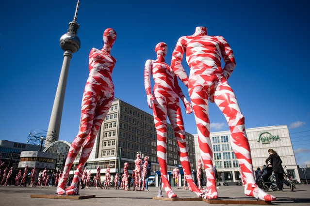 """Mannequins wrapped in warning tape, part of the Covid-19 memorial art installation """"It is like it is"""", stand in front of the TV tower and the world time clock on Alexanderplatz square in Berlin, Germany, 02 April 2021. German artist Dennis Josef Meseg presents display dummies in public places, as former pre-pandemic shopping symbols, wrapped in warning tape symbolizing the restricted life and curtailed basic rights. (Photo by Clemens Bilan/EPA/EFE)"""