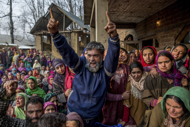 A Kashmiri villager shouts freedom slogans during the funeral procession of Asadullaha Kumar in Mandhaal village, some 70 Kilometers south of Srinagar, Indian controlled Kashmir, Saturday, December 3, 2016. Hundreds of angry villagers blocked the Srinagar-Jammu highway for hours alleging Kumar was tortured and then shot by Indian forces while he was performing his duty as a security guard at a government fishery. Police officers denied the allegation and said he was killed in cross-firing during an overnight counter-insurgency operation in south Kashmir. (Photo by Dar Yasin/AP Photo)