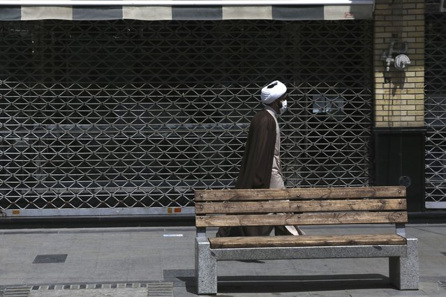 A cleric walks past a closed shop of Tehran's Grand Bazaar, Iran, Saturday, April 10, 2021. Iran on Saturday imposed partial lockdown on businesses in major shopping centers as well as intercity travels through personal cars in major cities including capital Tehran as it struggles with the worst outbreak of the coronavirus in the Mideast region. (Photo by Vahid Salemi/AP Photo)